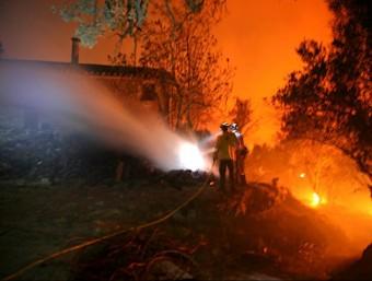 Dos bombers treballant en l'extinció de l'incendi en una masia dels Masos del Mig de Foixà JOAN CASTRO / ICONNA