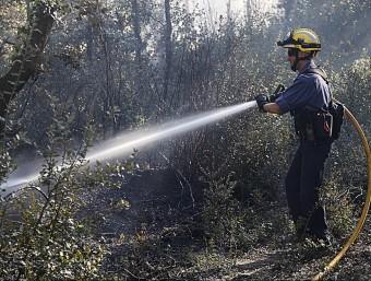 Un bomber remulla una de les zones afectades per l'incendi del Baix Empordà MANEL LLADÓ