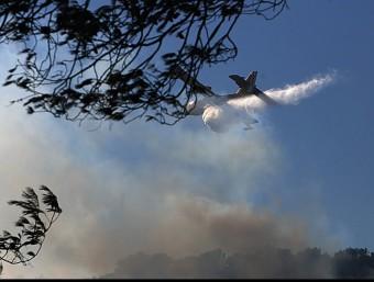 Una avioneta ruixant la zona afectada pel foc, aquest dimarts a la tarda MANEL LLADÓ