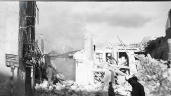 Soldats enmig de les runes de cases de la Granadella mentre un nen s'ho mira. AJUNTAMENT DE LA GRANADELLA