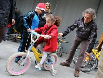 Una nena prova una de les bicicletes que l'ONG Bicicletes Sense Fronteres i BarcelonActua van entregar abans de Nadal al Raval de Barcelona QUIM PUIG