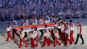 Un grup d'atletes russos porta la bandera del seu país després de despenjar-la de l'estadi olímpic durant la cerimònia de clausura REUTERS