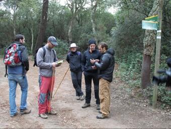 Excursionistes en un tram del camí consultant les guies CANAL AJUNTAMENT