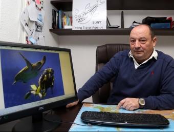 Vicente Vila, a la seu de l'empresa, mostra una foto d'una immersió al mar Roig.  JUANMA RAMOS