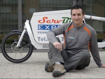 Joan Admetlla, amb la bicicleta que utilitza per fer el transport de paquets.  JUDIT TORRES