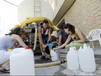 Escena de gent prenent aigua d'una cuba perquè l'aigua del pou té excés de nitrats.  ARXIU