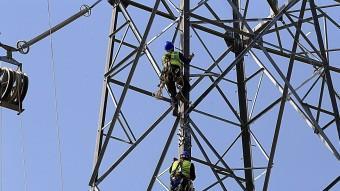 diferent operaris , aixecant una de les torres de la MAT. MANEL LLADÓ