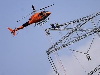 L'helicòpter acosta el cable als dos operaris, que el passen per una de les politges M. LLADÓ