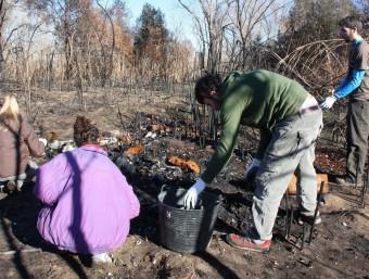 Joves voluntaris treuen ferralla, vidres, bombetes i trastos d'un dels abocaments incontrolats detectats al costat del riu Ter ACN