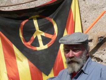 Lluís Hereu a casa seva a Vilobí davant la bandera confeccionada amb les quetre barres de Catalunya, el símbol de la pau i el triangle negre de l'anarquia. PAU LANAO
