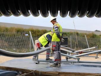 Els operaris desenrotllant el cable de la bobina  M. LLADÓ