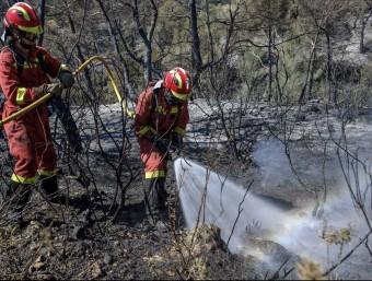 Un bomber remullant el terreny calcinat. SERGIO G. CAÑIZARES / EFE