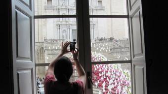 Una noia fa una foto amb el mòbil de les escales de la Catedral des d'una finestra de la Casa Pastors DANI VILÀ