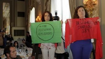 Dues activistes de la PAH mostren cartells contra els desnonaments durant la conferència de Miguel Arias Cañete, aquest divendres a l'Hotel Palace de Barcelona EFE