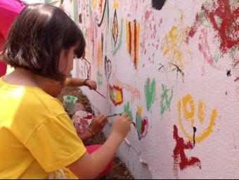 Unes joves participen en la pintada del mural de la Trobada. ESCOLA VALENCIANA