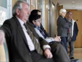 Xavier Soy assegut i Antònia Sánchez, dreta, se'l mira, als passadís del jutjat. LLUÍS SERRAT