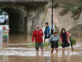 Diverses persones travessen una carretera inundada, aquest dilluns a Altafulla EFE