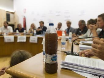 Una ampolla amb aigua tèrbola de l'aixeta d'una urbanització de Vidreres, a la taula dels regidors en l'últim ple de l'Ajuntament. GLÒRIA SÁNCHEZ/ ICONNA