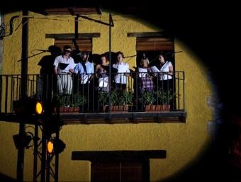 Un moment de l'actuació d'un grup de cantadors de Riudaura des d'un balcó de la plaça. EL PUNT AVUI