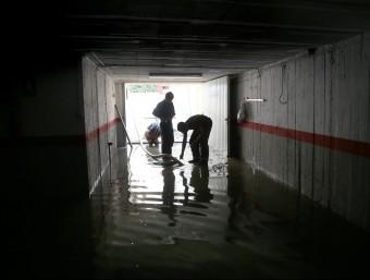 Bombers treballant en l'entrada a un pàrquing inundat a Palamós. JOAN CASTRO