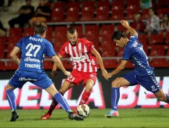 David Juncà intenta desfer-se de Quique Rivero i de Javi Moyano en el Girona-Tenerife de lliga. JORDI RIBOT / ICONNA