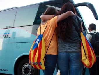 Dues persones es disposen a pujar a un dels autobusos que ha sortit des de València aquest dijous al matí per assistir a la Diada ACN