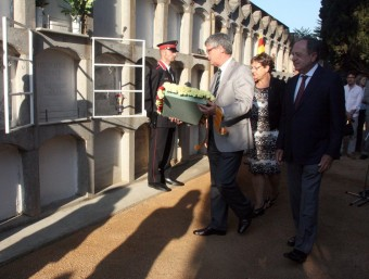 El delegat del Govern, Eudald Casadesús i el de la Diputació, Joan Giraut, portant ahir un dels rams de flors que van deixar als peus de la tomba d'Irla, a Sant Feliu de Guíxols. TÀNIA TÀPIA (ACN)