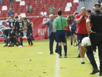 Després de l'1-1. Pitu Abelardo (dreta) amb les mans al cap, el delegat del Girona, Javier Galiano, pressionant l'assistent i els jugadors, celebrant el gol de Juncà. EL COMERCIO