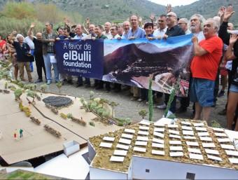 Els assistents a la trobada a la Cala Montjoi darrera la pancarta, i amb la maqueta de com quedarà el nou Bulli en primer terme. LLUÍS SERRAT