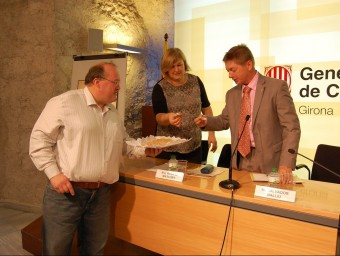 El pastisser Toni Noguera, oferint galetes d'avellana a Anna M. Mascort i Salvador Balliu, ahir a Girona J.C.C