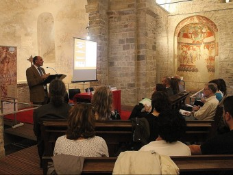 Manuel Castiñeira fent la seva xerrada i, al fons, el mural romànic de Sant Tomas Becket J.ALEMANY