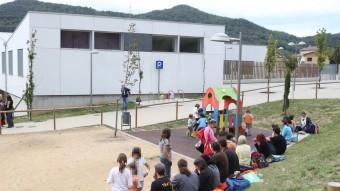 Familiars i mainada als afores del centre d'ensenyament del barri del Morrot d'Olot, a la sortida dels alumnes a la tarda. JOAN CASTRO / ICONNA