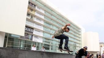 Un patinador salta el gran banc de pedra que transcorre paral·lel a la façana principal del MACBA, a la plaça dels Àngels, observat per dos col·legues QUIM PUIG