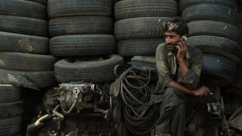 Un treballador parla pel seu Iphone en un dipòsit de ferralla de Mumbai PUNIT PARANJPE/AFP