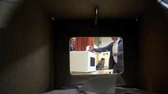 Una urna plena de paperetes, a través de la qual es veu un home votant el 9 de novembre QUIM PUIG