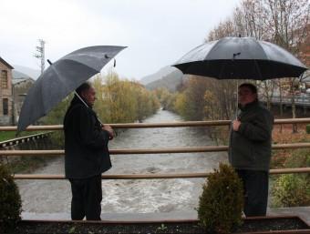 Dos homes miren el riu Freser, a Campdevànol aquest dissabte al matí ACN