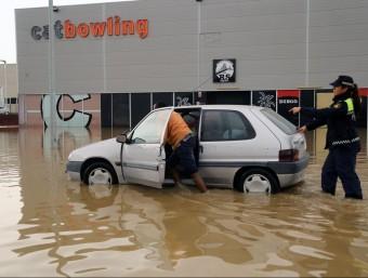 Un veí mirant de treure el cotxe del carrer inundat davant dels cinemes de Figueres.  MANEL LLADÓ