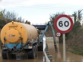 Un camió drena aigua a Pont de Molins.  GLÒRIA SÁNCHEZ/ ICONNA