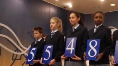 Els nens del col·legi de San Ildefonso mostren el número del primer premi, aquest dimarts durant el sorteig de Reis ACN