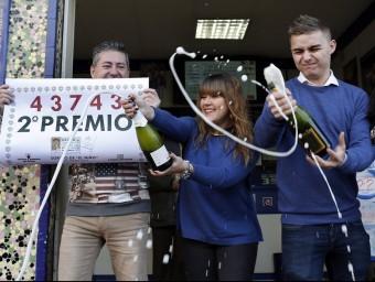 Els responsables d'una administració de loteria de València celebrant la venda del segon premi JUAN CARLOS CÁRDENAS / EFE