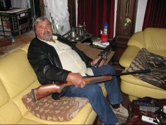 El veí de Calonge assaltat fa poc més d'un any, en una foto de fa pocs dies a la sala d'estar de casa seva amb una escopeta de balins i un ganivet de grans dimensions ÒSCAR PINILLA