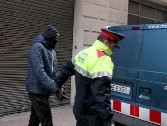 Un agent dels mossos traslladant a una furgoneta policial un dels detinguts en el dispositiu contra la banda dels Lobos callejeros ACN