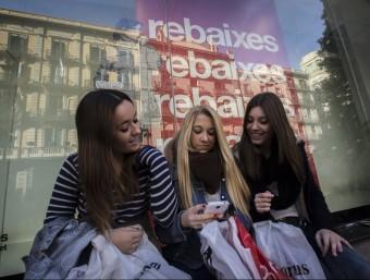 Un grup de noies consulta el seu 'smartphone' a la porta d'una botiga de roba.  ALBERT SALAMÉ