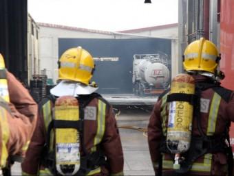 Dos bombers observen l'interior de la fàbrica on hi ha hagut la deflagració al polígon de les Comes ACN