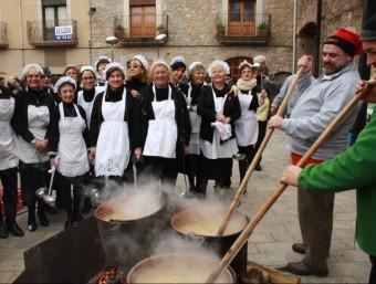 Dos cuiners , remenen l'olla de la Sopa de Verges, ja falta poc per posar-la al plat. JOAN PUNTÍ / JOAN CASTRO (ICONNA)