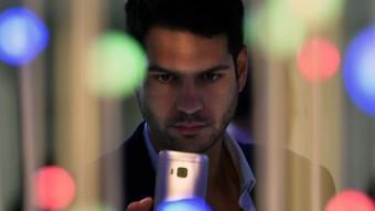 Un visitant observa un telèfon durant la jornada d'ahir del Moblie World Congress. LLUÍS GENÉ / EFE
