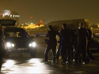 Imatge d'un dels fèretres transportat cap a un cotxe funerari després de l'arribada a l'aeroport del Prat ACN