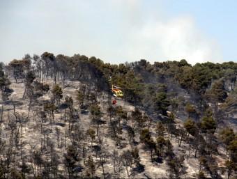 Un helicòpter dels Bombers sobrevola la zona cremada aquest dilluns a Rocallaura, a Vallbona de les Monges ACN