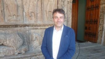 Jordi Munell, fotografiat davant la portalada del monestir. J.C