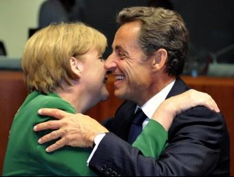 L'aleshores president francès, Nicolas Sarkozy, fa un petó a la cancellera alemanya, Angela Merkel, en una cimera de la UE.  REUTERS